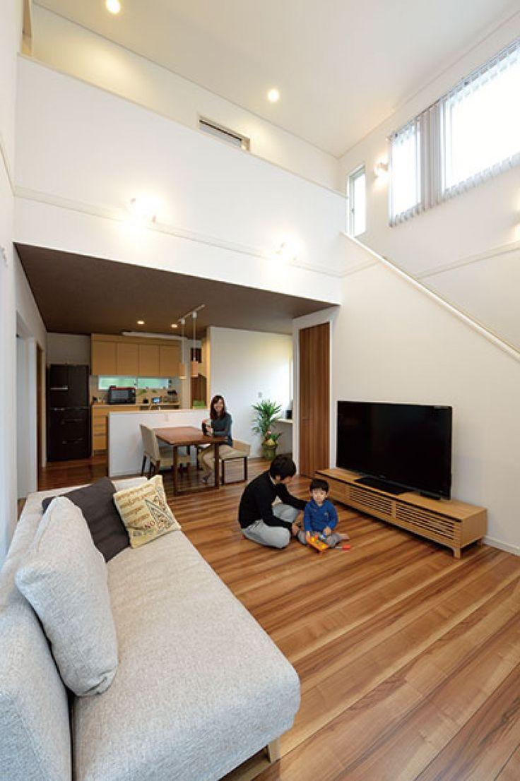 ご夫妻が希望したリビング階段のあるLDK。正面奥が対面キッチン。吹抜けの高窓から陽の光がたっぷりと射し込み、白い壁がいっそう明るさをもたらしている。室内のデザインテイストは、子どもと一緒にのんびり寛げる空間を希望してナチュラルモダンなイメージにコーディネート。