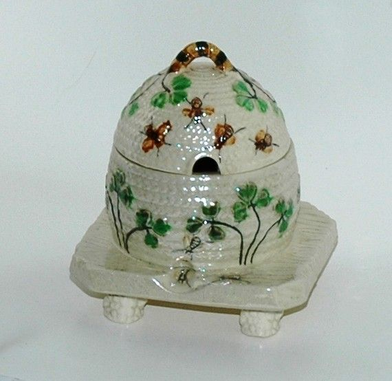 Cute honey pot is covered with clover leaves and bees, all hand-painted. Its a beehive, or skep sitting on a raised platform with three little