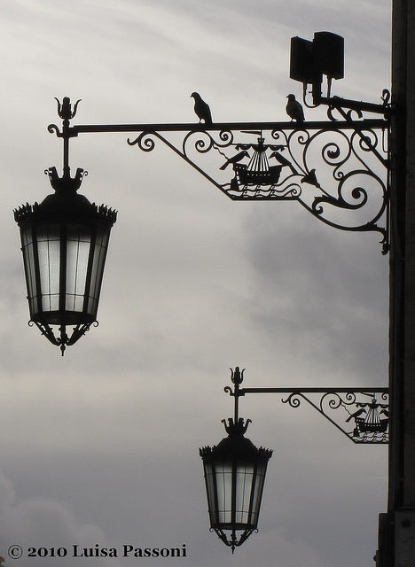 Another street light in Lisbon, Portugal, ornamented with pigeons and a ship