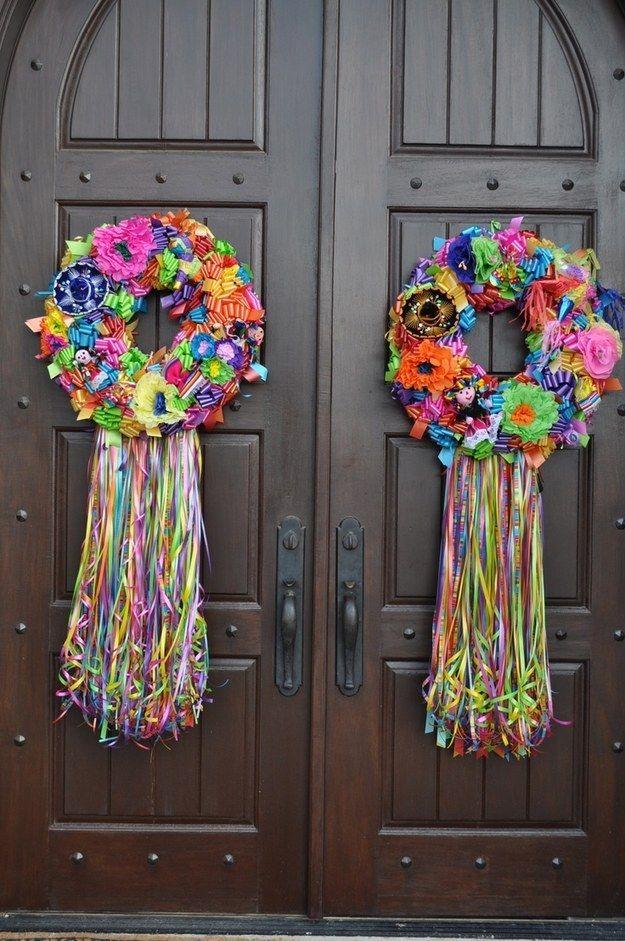 Haz una corona con flores de papel y distintos accesorios típicos para recibir a tus invitados con estilo.