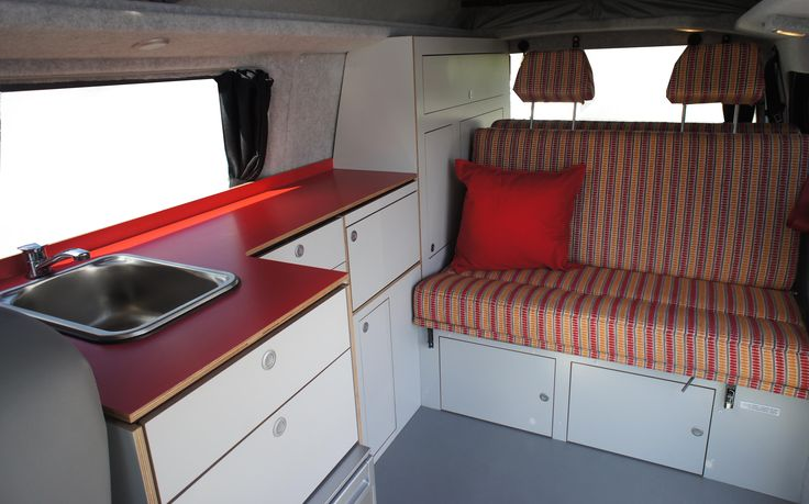 VW T5 Campervan interior with red bench top and grey cabinetry.