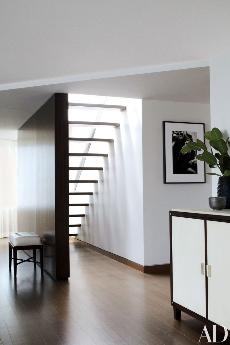 A zebrawood partition hides a discreet staircase with walnut treads; the photograph is by Pamela Hanson, and the credenza is by Mattaliano. | archdigest.com