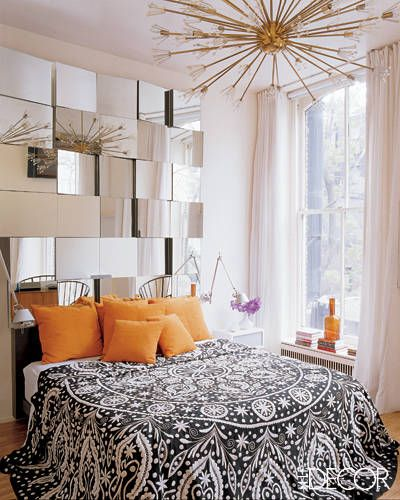 Mod, Mod World    Fashion designer Naeem Khan and interior designer Tom Scheerer combined forces to create this wall sculpture of mirror panels, which serves as a mod headboard in Khan's New York loft. The vintage chandelier is by Lightolier, and the bedding was custom made by Naeem Khan Home.