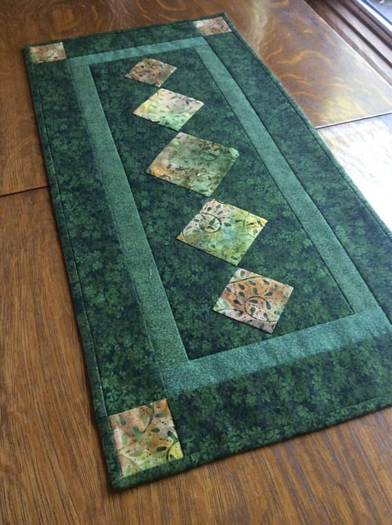 Beautifully designed table runner in lovely greens.  https://www.etsy.com/listing/548147916/green-table-runner-batik-table-runner?ga_order=most_relevant&ga_search_type=all&ga_view_type=gallery&ga_search_query=quilted%20table%20runners&ref=sr_gallery-12-3