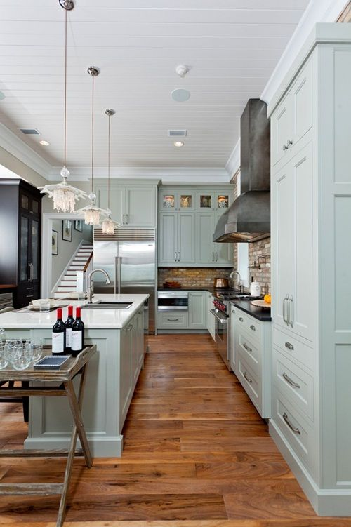 mission cabinets to the ceiling, sink within long island, brick/stone backsplash coordinates with wood flooring