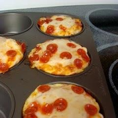 Cupcake Mold Pizzas .....  Pillsbury Refrigerated Pizza Dough  Pizza Sauce  Shredded Cheese  Pepperoni  Cupcake Tin  Preheat oven to 425 and grease the cupcake pan.  separated dough into 4 equal parts; pan. Push the dough into the molds; try to make the dough cover the sides.  Cover dough with pizza sauce, cheese and pepperoni.  Bake for 10-15 minutes. Since mine were in larger molds they didn't cook through all the way, but other than that they were amazing!