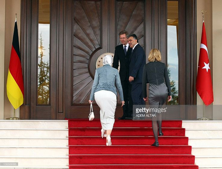 German President Christian Wulff (2nd L) and his Turkish counterpart Abdullah Gul (2nd R) wait for their wives Bettina Wulff (R) and Hayrunnisa Gul (L) to join them in front of the Presidential Palace in Ankara on October 19, 2010. Wulff began talks with Turkish leaders on October 19 as debate simmered in his country on how Muslim immigrants, many of them Turkish, should be integrated.