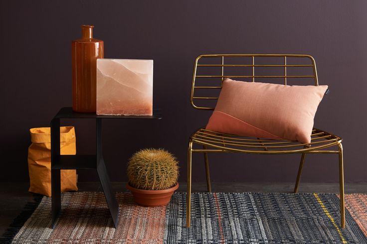 De donkere versie van Zomer Zon, met als warme basiskleur voor de muur de bruin/aubergine kleur TC17032. Contrastwerking door de kleuren nude (zoutsteen, tapijt en kussen) en goud en (stoel) en oranje (papieren zak). De sfeer ademt modern 50-ties uit.