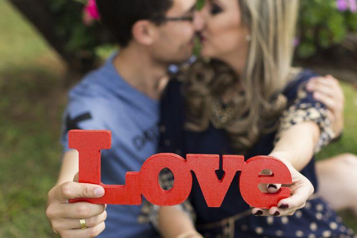 o destaque da palavra Love, sendo segurada e ao fundo desfocado William e Driely em um quase beijo