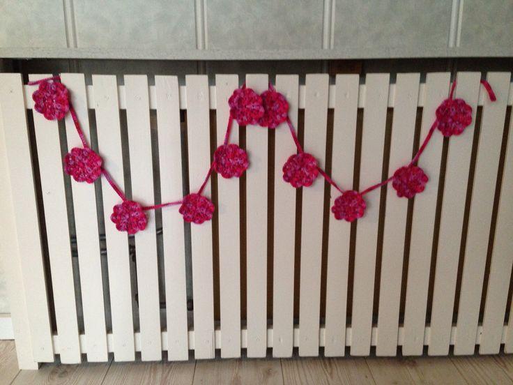 Gehaakte slinger van 11 roze bloemetjes. Ongeveer anderhalve meter lang. Te koop via marktplaats.