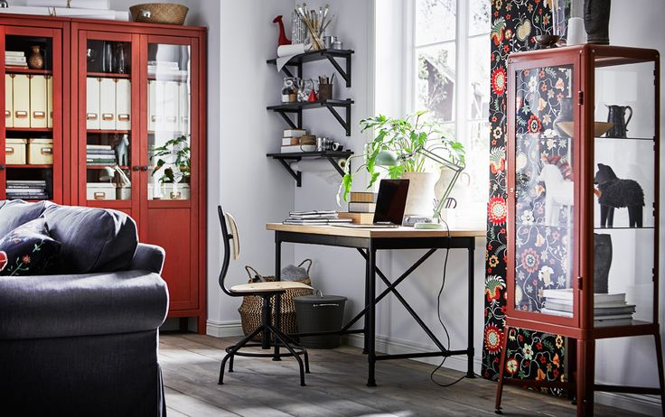 Industrial style desk and swivel chair in pine/black in a living room with red/brown.