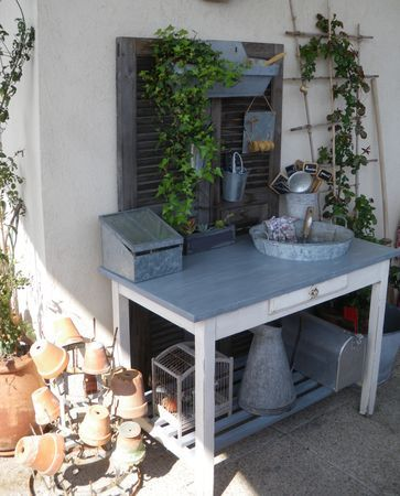 potting table from a drafting desk.  I love the old tin things and the shutters on the back.