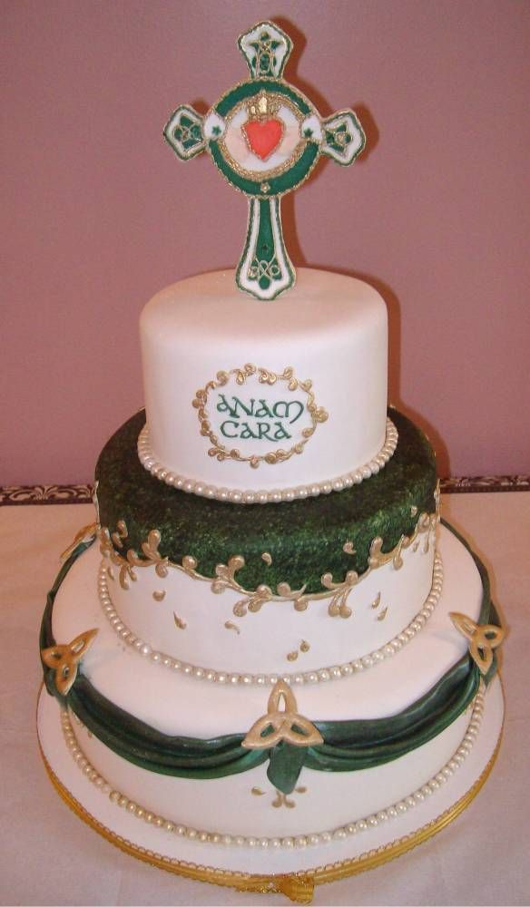 Gorgeous Celtic-symbol wedding cake adorned with trinity knots and Irish Celtic cross bearing a claddagh. Made by