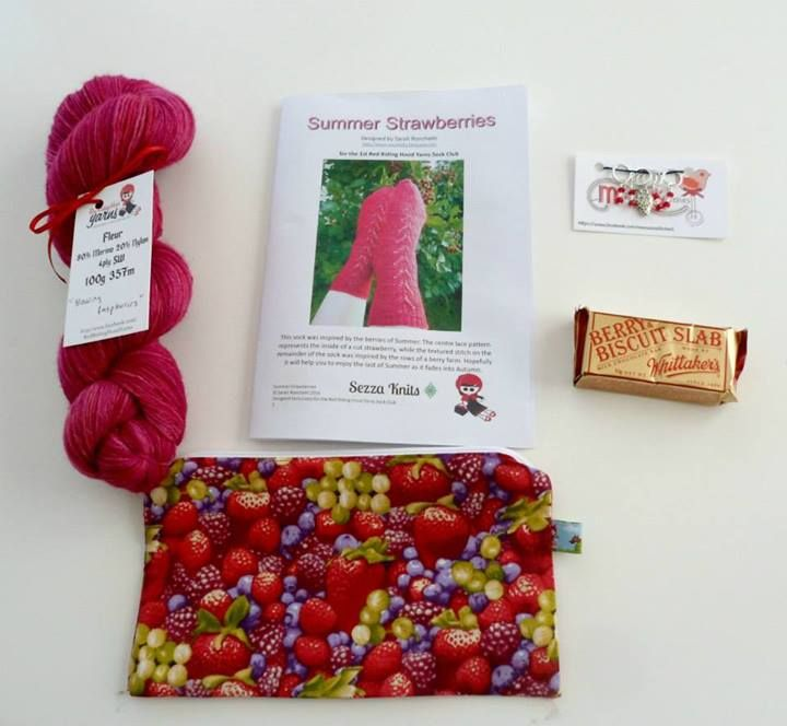 "Treat Your Feet Yarn Club 2014 - Berrylicious. Raspberry pack includes: ""Raspberries"" yarn, Zippy Wippy, ""Summer Strawberries"" sock pattern, Mamas in Stitches stitchholders, and Whittakers Chocolate Slab 