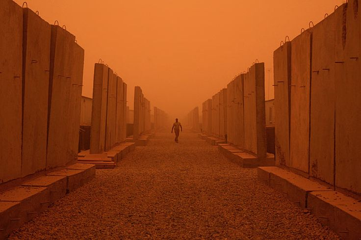 An American soldier with the 25th Infantry Division walks between concrete blast walls that protect their barracks during a sand storm in Camp Liberty, Baghdad, Iraq on July 1, 2008.