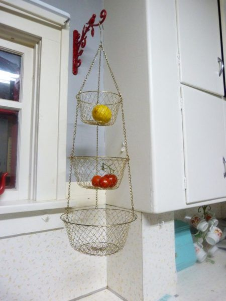 produce storage solution: hang 3-tiered wire baskets on a hook in the kitchen