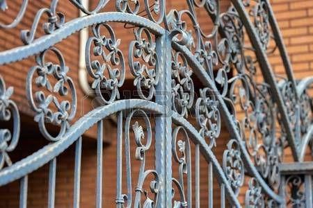 rejas de hierro: Valla de hierro fundido de los ladrillos rojos de fondo urbano Foto de archivo