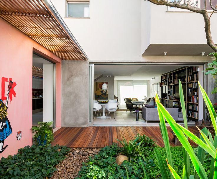 リビングと全開口のスライドドアでつながるウッドデッキのテラスと緑あふれる庭