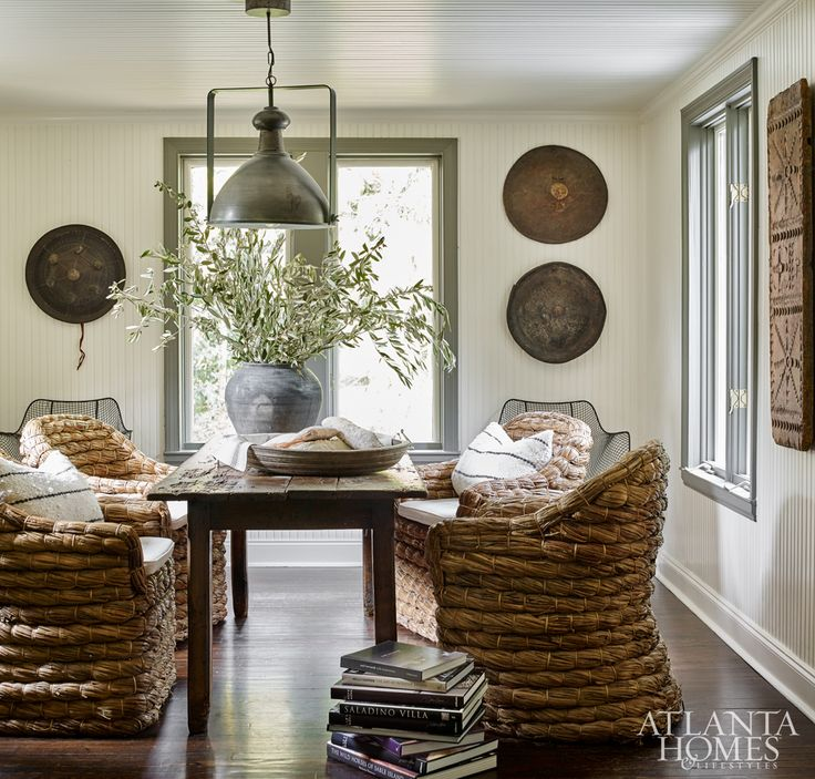 The breakfast room was the only spot where the Weitzes left the original pine floors, so they opted for color in the form of the dark-gray window trim instead. Chairs, pillows, African hats and jar through B. D. Jeffries.
