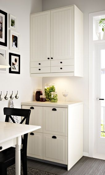 Wall cabinets mounted above free standing base cabinet with four visible drawers