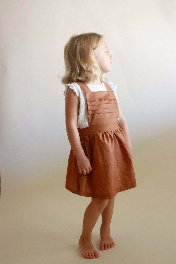 The Schoolhouse Pinafore is an incredibly versatile piece that can be dressed for all seasons. It boasts horizontal pleats, crossed straps, and a gathered skirt; features that keep it simple yet stylishly timeless. Perfect for school, church, or outside play, its a piece your little one will absolutely love.      SKILL LEVEL: Beginner    SUITABLE FABRICS: Most materials! Anything with a nice drape and bit of body. Light, medium, and heavy-weight cottons, medium to heavy-weight knits…