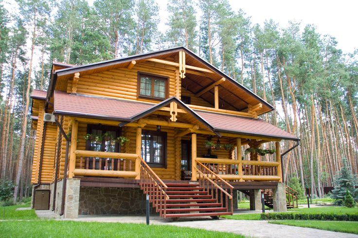 2-story log home with front porch and second floor covered deck.