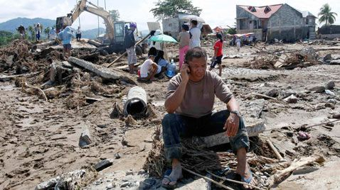 This photo is powerful because it shows a man sitting in an area of ruins where it looks like a house used to be  Philippine Typhoon News Today | Philippines Typhoon Flooding