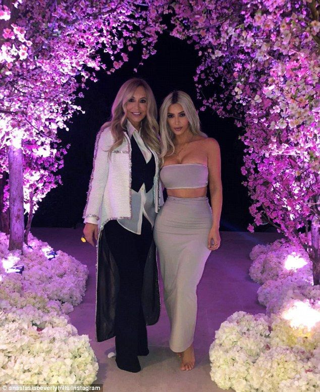 Blooming lovely: Kim Kardashian was the star of the show during her over-the-top cherry blossom-themed baby shower in LA on Saturday. She is pictured with cosmetics mogul Anastasia Soare