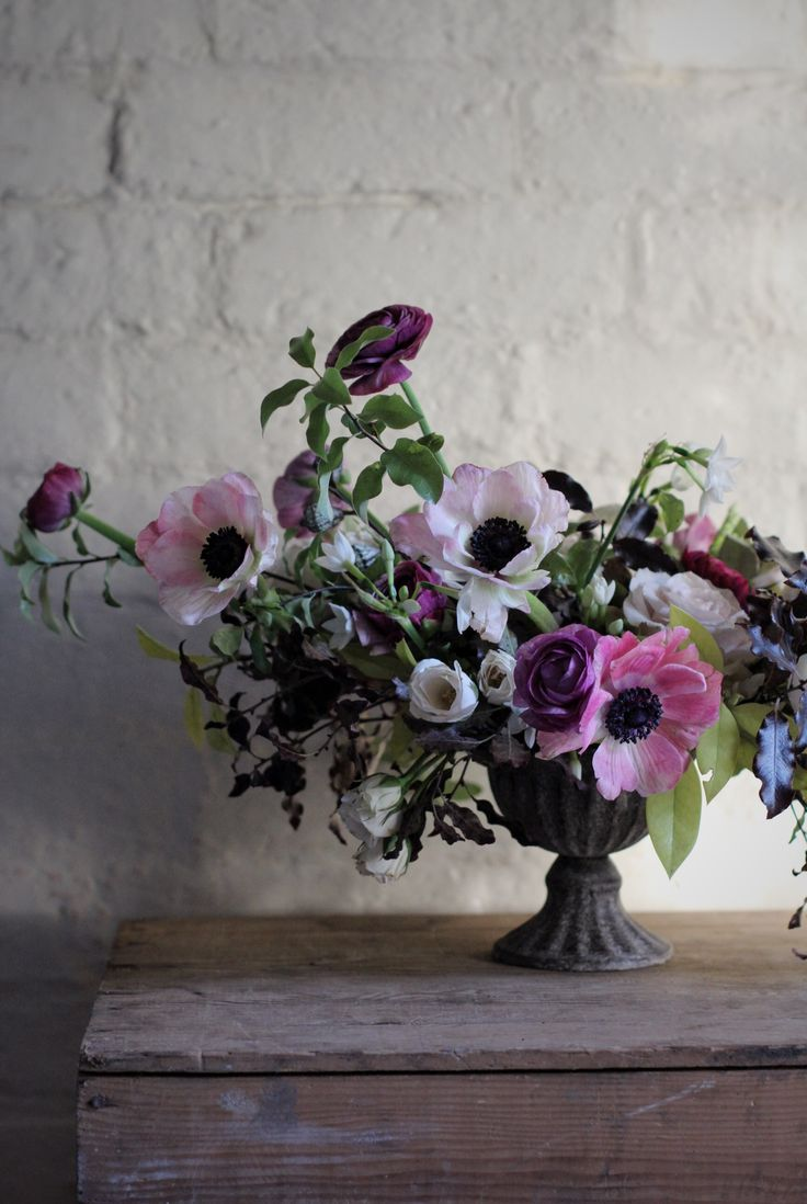 A floral wedding table arrangement by Kent florist Jennifer Pinder. This arrangement would be perfect for a winter wedding (created in early January) using pink anemones, narcissi, quicksand roses, plum ranuncuus and foliage foraged from the garden. Jenn Pinder hosts floral workshops for hobbyists and florists and does wedding flowers across the UK.