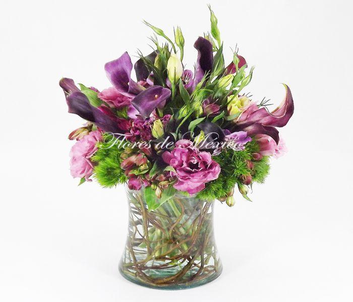 Exóticas calas moradas acompañadas de lisiantus, florero transparente que permite ver el efecto de raíces. Arreglo para gustos exigentes.