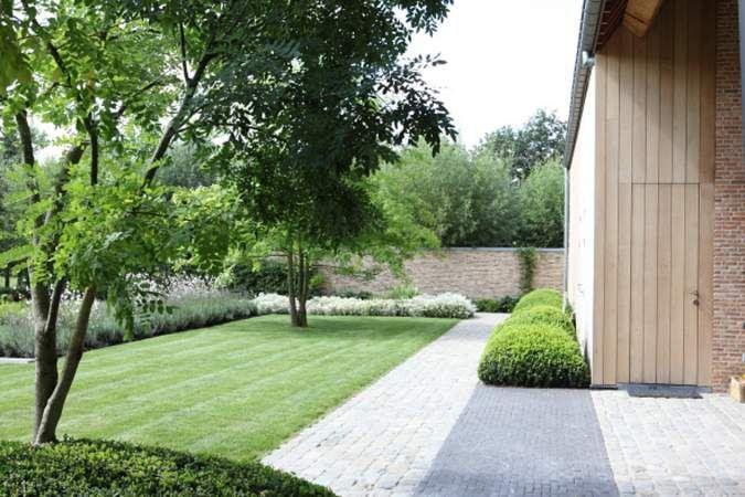 Deze in hoevestijl gebouwde nieuwbouwwoning is zo gepositioneerd dat de zichtlijnen geprojecteerd zijn op het omliggende landschap. De weidse uitzichten zijn daarom ook bepalend geweest bij de inrichting van de tuin. Het hoger gelegen niveau rond de woning is gedetailleerder ingericht waarin op diverse plaatsen sfeervolle terrassen zijn aangelegd. Het lager gelegen deel van de tuin is ruimtelijk, landschappelijk en sober met fraaie doorzichten op de aangrenzende paardenweiden.