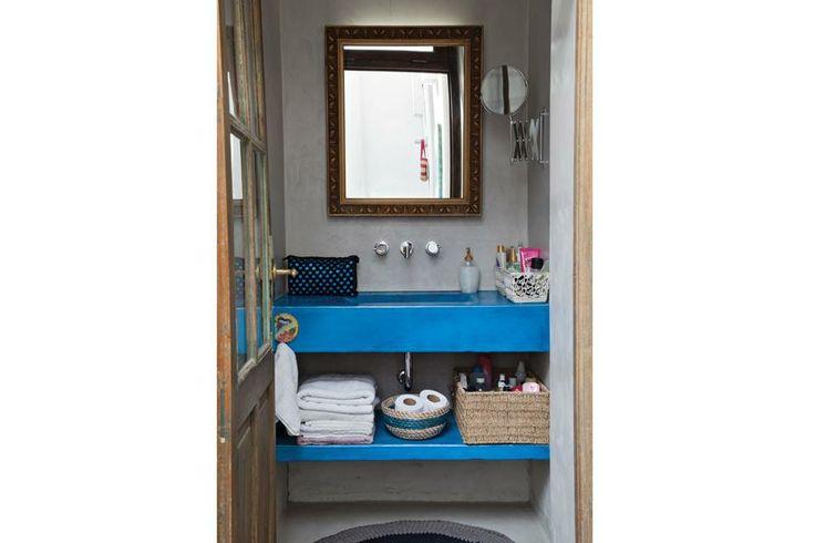 El microcemento es un material de bajo costo al que se le puede sumar color. En este baño, el azul de la bacha contrasta con el gris neutro ...