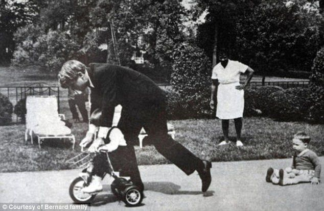 Remembered: Bobby Kennedy playing with two of his children, with Ena it the background. Wife Ethel and eight of his children attended Ena's funeral Thursday