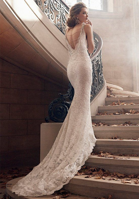 This is more about the back and the fact that she's standing atop the stairs so the train gets the full effect. DROP DEAD GORGEOUS! Ivory/Silver alencon lace trumpet bridal gown, V-neckline with beaded necklace at back, jeweled appliques at natural waist, chapel train.
