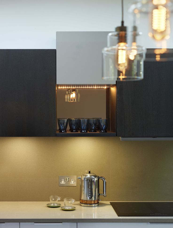 The elegant, downlit mirrored shelf created in this kitchen by Connaught Kitchens shows that storage can be both practical and a striking design feature