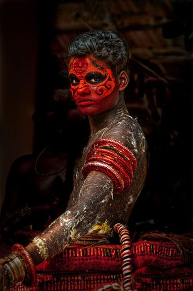 Theyyam in Transition ~ a dancer from the Malabar Coast in south India (Theyyam are 'holy men' or priests who dress in fantastic costume once a year to participate in temple ceremonies.)