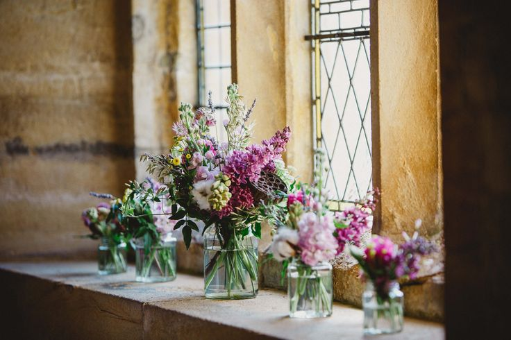 Rustic wedding flowers in cute little jam jars, scattered all over the window ledges of the village church.