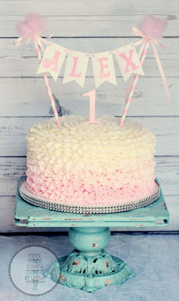 Pink ombre buttercream ruffles cake with bunting.  1st birthday