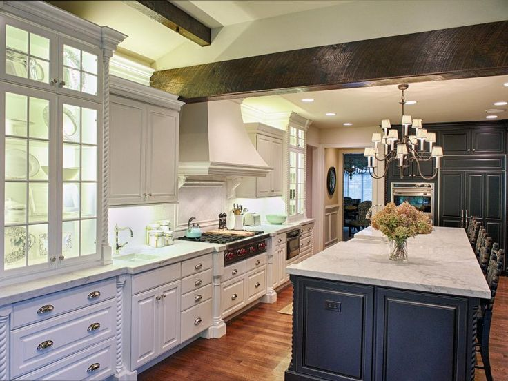 Wood support beam and a classic chandelier paired with a mix of black and white cabinets make this a warm, classic space.  The white cabinets provide a highlight feature, while the upper and lower cabinetry lights create the perfect ambiance. The large island with marble countertop provides plenty of space to work and eat.
