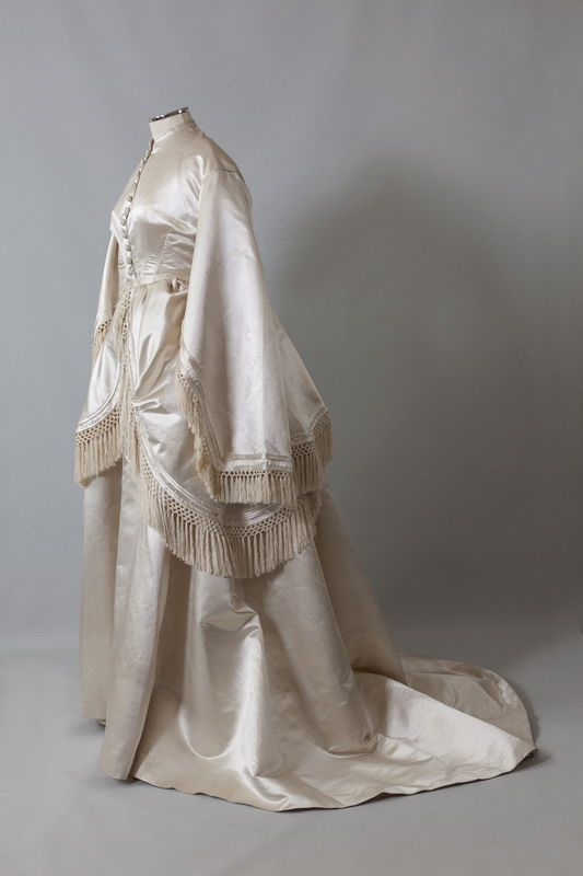 Wedding dress, 1868. Ιvory satin trimmed with silk fringe. Three pieces: bodice, skirt with train and overskirt.