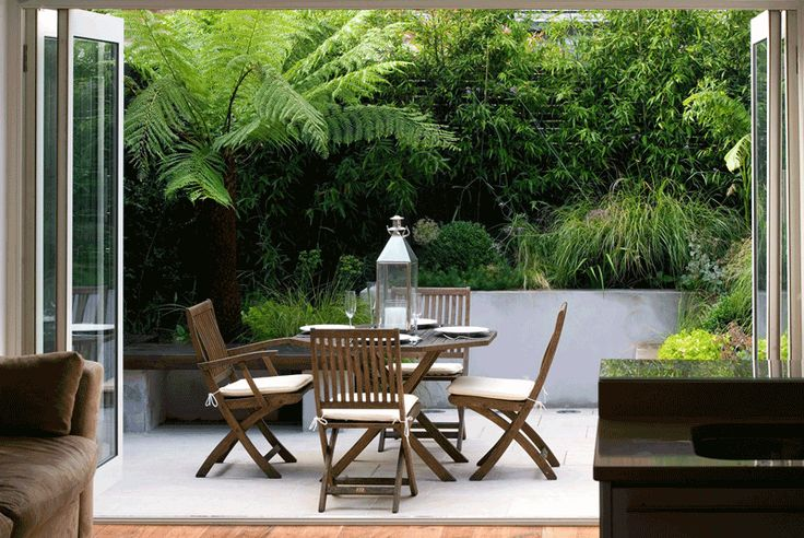 Chic little courtyard in Fulham with lush planting. Project by Charlotte Rowe