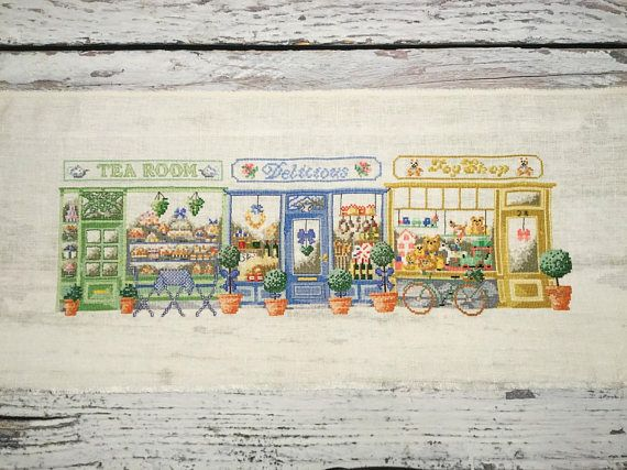Shopping street with tea room, delicatessen and toy shop.  Cross Stitch Sampler . Unframed Finished Completed Cross Stitch . Shopping Street . Permin of Copenhagen .