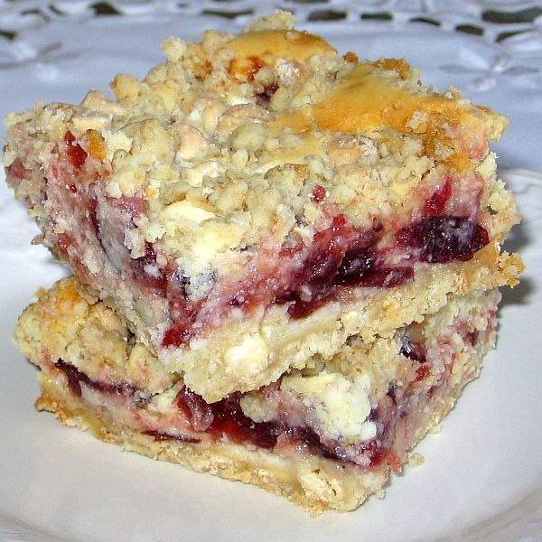 This recipe for cheesecake cranberry bars features a streusel topping made with oatmeal and white chocolate chips.
