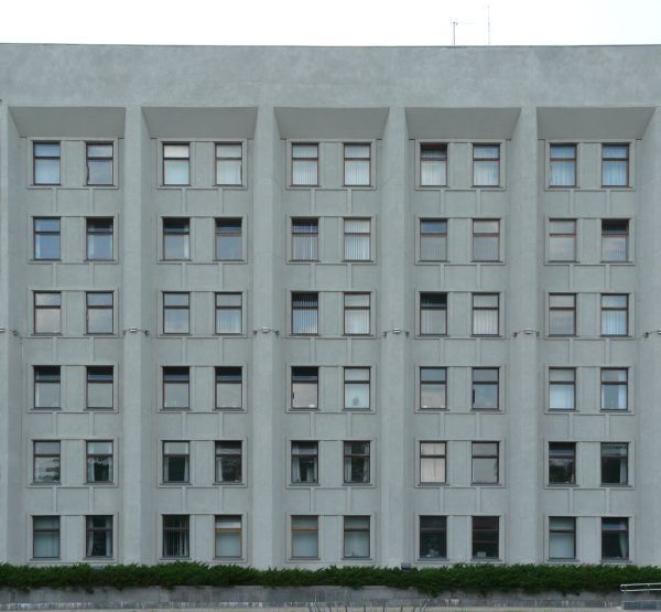 Large, multi-storey building of dull, grey concrete with windows.