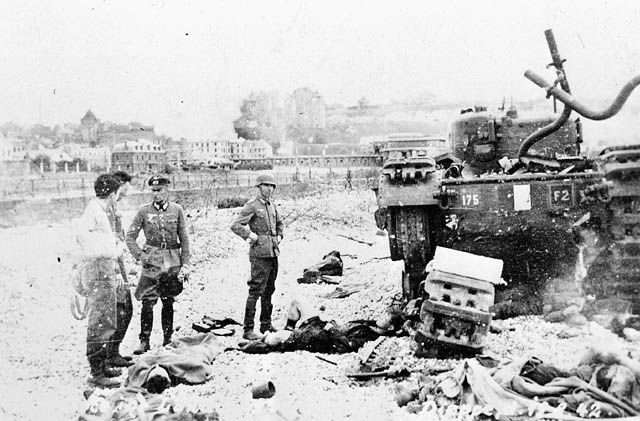 Canadian prisoners of war & German soldiers surveying the destruction around them on the beach at Dieppe