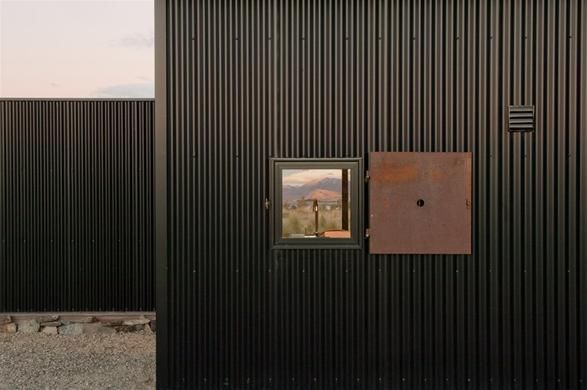 Weathered steel hinged window covering at Tekapo Shed, a corrugated steel cladded retreat by C Nott Architects in New Zealand.