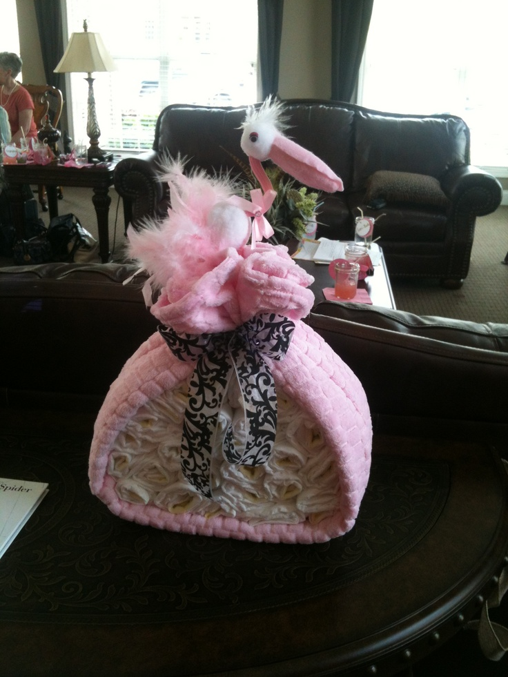Stork head from party city with a baby blanket and ribbon around diapers