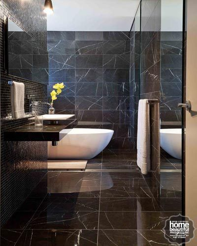 Top-to-toe polished Pietra Grey marble from Marble & Ceramic Corp lines the floor and walls of this moody modern bathroom.