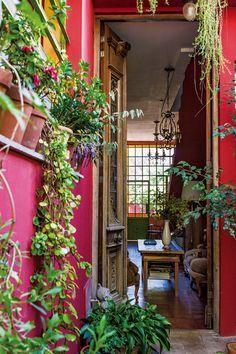 Hall de entrada colorido en tonos fucsia y rojo, con muebles de madera vintage. En la casa de la fileteadora Silvia Dotta. #jardinespatios