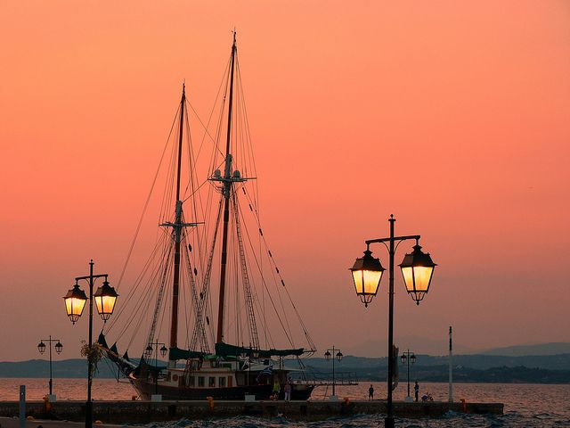 Sunset on Dapia with traditional vessel and lamp posts - Spetses island, Saronic Gulf, Greece